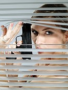 Woman´s portrait while looking out the blinds and holding the gun