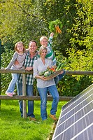 Happy family standing near solar panel holding garden vegetables