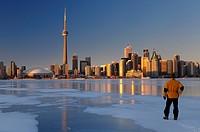 Man standing on frozen Lake Ontario ice looking at Toronto city skyline at sunset