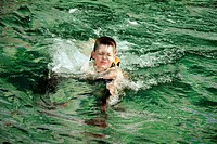 Boy eyes closed swimming with dolphin