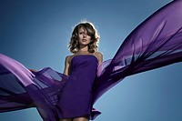 Young woman wearing a purple dress with billowing fabrics