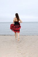 Young woman in red dress running towards the water
