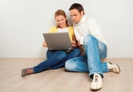 Smling couple looking and laptop screen