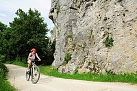 Female cyclist passing rock face, Altmuehltal cycle trail, Altmuehltal natural park, Altmuehltal, Bavaria, Germany