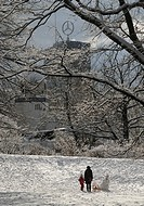 Woman and child, sled and snowman in the snowy Grosser Tiergarten in front of an animal enclosure of the zoo and the Europa Center with Mercedes star,...