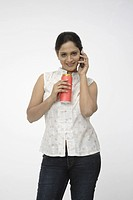 Young girl holding cold drink can in one hand and mobile in other hand MR 703C