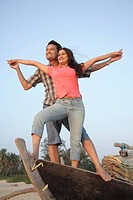 South Asian Indian young man and woman standing on wooden boat at front view holding and spread hands looking toward on seashore, Shiroda , Dist Sindh...