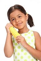 Eight year old girl holding sweet corn in both hands near her cheek MR703U