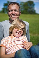 Portrait of father with son looking at camera and laughing