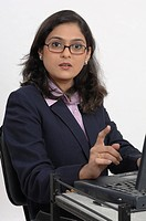 Office going South Asian Indian lady pointing finger using laptop MR_670T