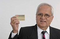 Office going South Asian Indian active old man showing credit card MR670R