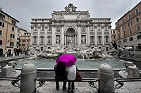 Image with low color saturation of a couple sitting in front of the Trevi Fountain on a hot pink umbrella on a rainy day