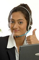 Young girl using headphones with microphone showing thumb sign working in call centre MR748O