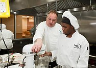 Roseville, Michigan - Instructor John Adamski works with a student preparing food at the Dorsey Culinary Academy, a private career training school