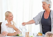 Aged woman serving her daughter at home