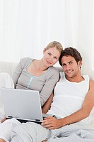 Adorable couple looking at their laptop on the bed at home