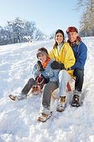 Family Enjoying Sledging Down Snowy Hill