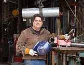 Mixed race machinist holding helmet