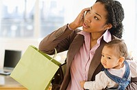 Mixed race woman holding baby and talking on cell phone