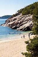 Visitors play at Sand Beach in Acadia National Park near Bar Harbor, Maine