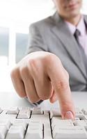 Vertical image of male finger pushing key of enter