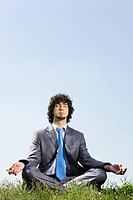 Image of businessman doing yoga in a natural environment