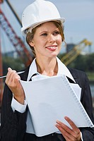 Portrait of beautiful engineer holding architectural project and pen