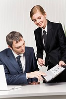 Photo of confident boss looking at documents being shown by his secretary