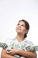 Portrait of charming lady holding bills of dollars and looking upwards