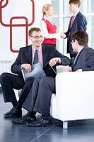 Two businessmen are negotiating on the background of people shaking each other´s hands