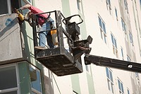 Male worker installs siding during renovation of McKinley Tower aprtments formerly the MacKay Building in downtown Anchorage, Southcentral Alaska, Sum...