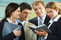 Confident smiling professionals are discussing a conditions of contract on the background of building