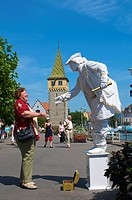 Street performer, living statue in front of the Mangturm tower at the harbor, Lindau, Lake Constance, Bavaria, Germany, Europe