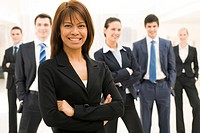 Portrait of successful businesswoman looking at camera with her workteam at background