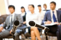 Image of two microphones on background of people listening to lecture at conference