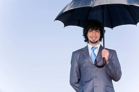 Image of successful businessman under his umbrella of background of sky
