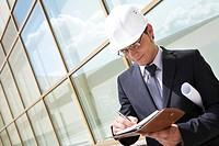 Portrait of confident foreman in helmet writing business plan