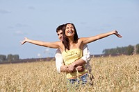 Image of joyful girl stretching arms while being embraced by her boyfriend