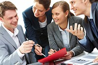 Photo of business partners showing document to their boss at meeting