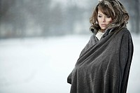 Young woman in the snow, wrapped in a poncho