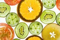 Slices of fruits and vegetables: kiwi, orange, apple, tomato, cucumber
