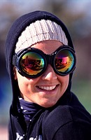 Portrait of a young woman smiling, wearing big reflecting sunglasses a white cap and a blü hood over it