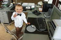 Infant with shirt and bow tie at the desk