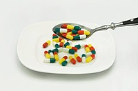 Tablespoon full of capsules in front of a plate with capsules