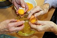 Hands of elderly women separating egg yolks from egg whites, baking an apple cake during an activity hour in a nursing home