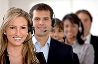 business customer support team in an office with headsets .