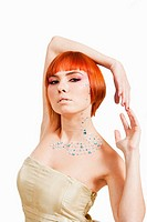 Beautiful redhead Caucasian girl with rhinestones and arms around her head, isolated