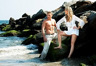 Caucasian guy and girl together on rock formation next to ocean water  Female is wearing long white shirt  Both standing on rocks at the beach  Guy sh...