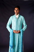 Beautiful authentic Indian hindu man in typical ethnic groom attire standing with hands together  Bangali male wearing a light blue agua decorated Dho...