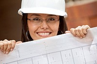 Female architect with blueprints at a construction site